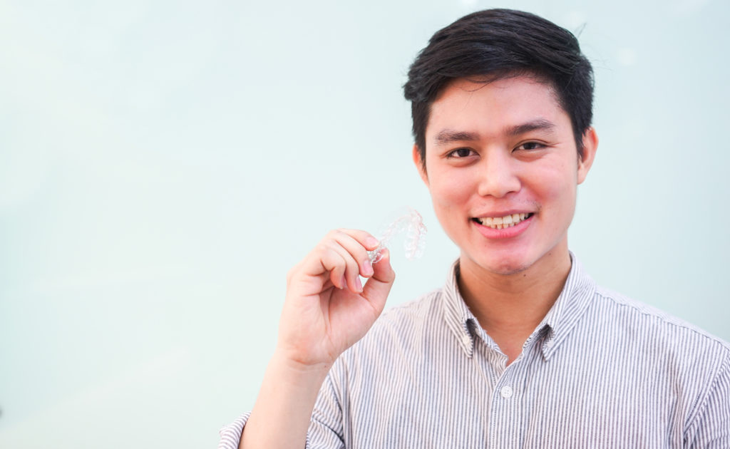 young man smiling holding Invisalign aligner