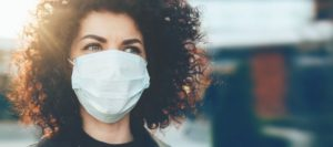 At-risk woman wears mask in COVID-19 as recommended by Marlton, NJ dentist